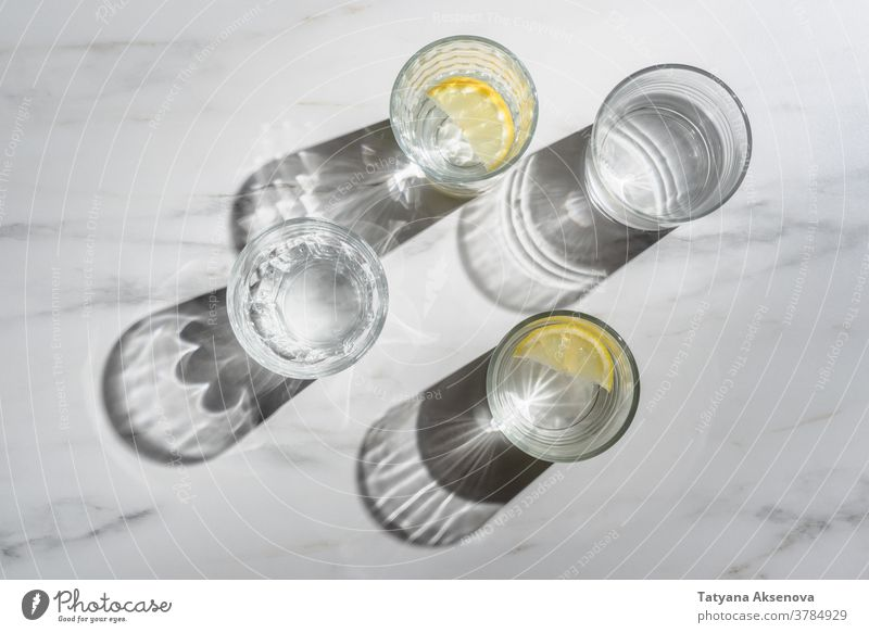 Glass of water with lemon pieces on marble background. Immune boosting morning drink fresh fruit glass cold citrus beverage