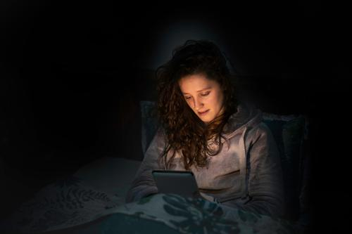 girl reading her tablet or ebook in bed before sleeping indoors rest female bedtime evening leisure browsing lying lifestyle one home bedroom mobile dark night