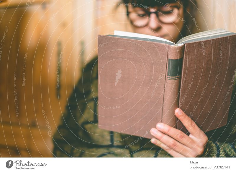 A woman with glasses is reading a book at home Reading Book Eyeglasses Bookworm Cozy Reading matter Novel Education Literature hollowed concentrated Sweater