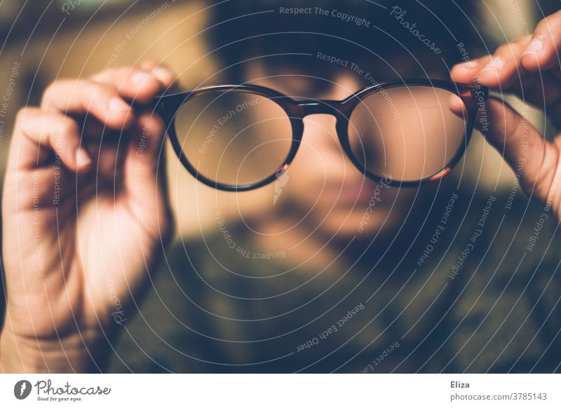 A woman takes off her glasses Eyeglasses Vista Observe look at decrease Woman Person wearing glasses blurred Vision visually impaired