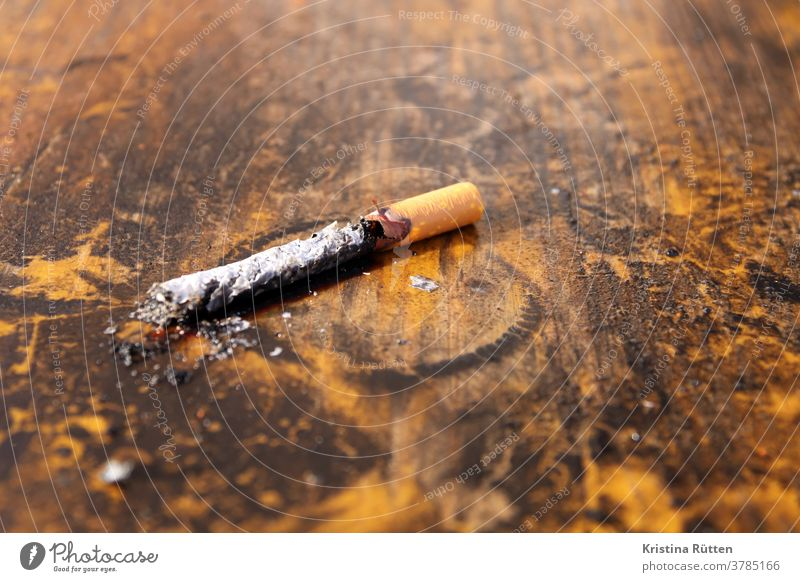 burnt cigarette on wooden table Cigarette tilt cigarette butt Burnt out burnout Completed in the end charred fired with coke burn out Filter cigarette filters