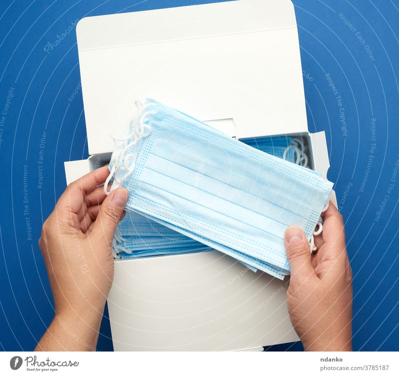 box with disposable medical masks and two female hands, blue background hold medicine pandemic pneumonia prevention protect protection protective quarantine