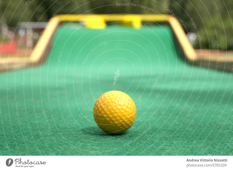 close up on a minigolf ball on the course with copy space for your text outdoor outside no people nobody color image fine art print wall print play playing fun