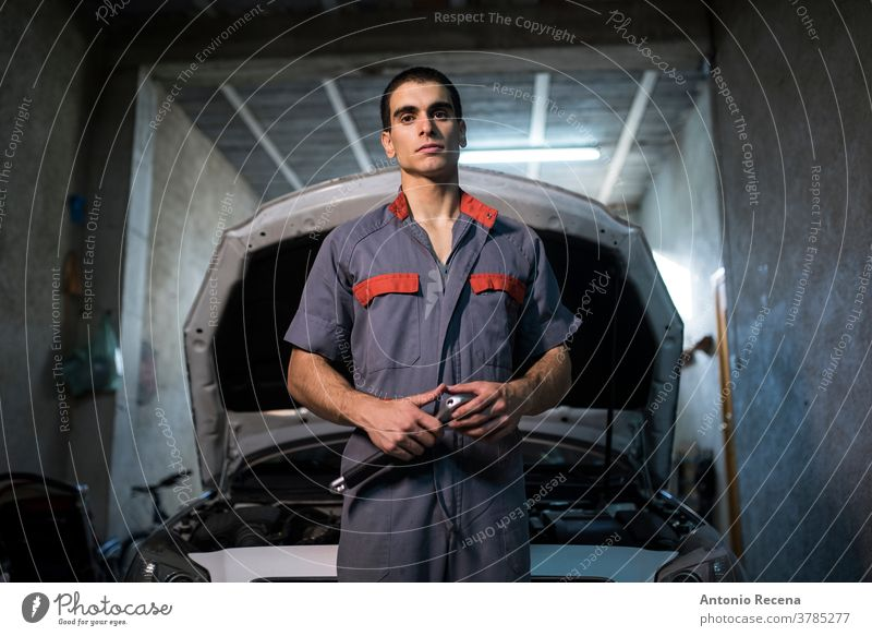 young male mechanic works in his home workshop man garage men adult attractive handsome lifestyles worker employee people job occupation car looking at camera