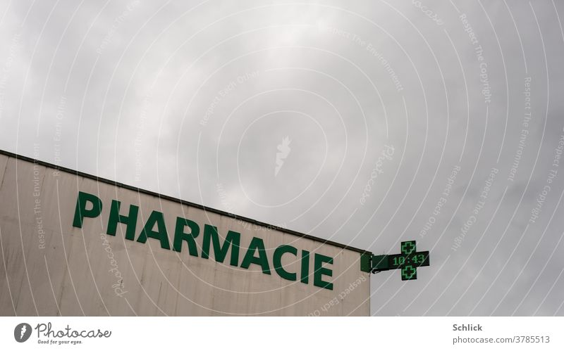 Pharmacy in Lorraine with lettering Pharmacie and neon sign with time much overcast sky France Green Modern Sky Neon sign Time Crucifix Covered Concrete