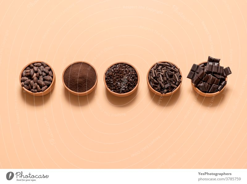 Cocoa and chocolate ingredients in bowls. Cacao beans and chocolate assortment top view above view aligned background baking beige bitter cacao cacao beans