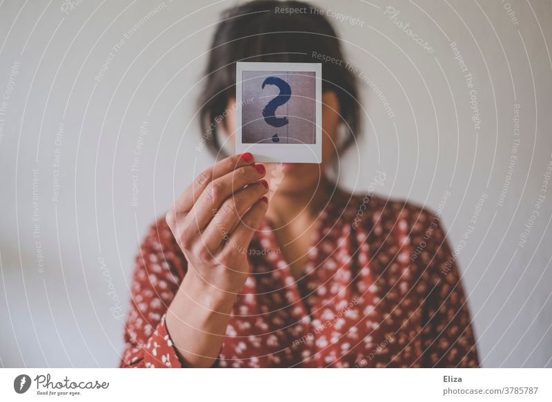 Identity crisis. Young woman holds a Polaroid with a big question mark in front of her face. identity crisis Human being Woman Question mark helpless Insecure