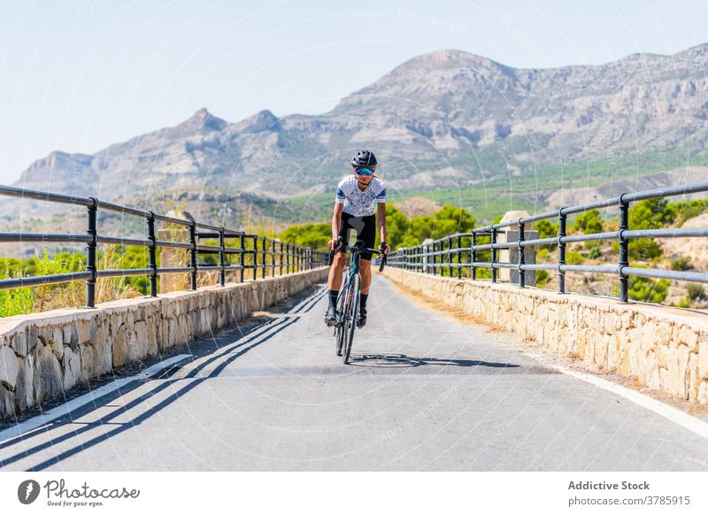 Cyclist riding bike on rural road in highlands cyclist ride mountain bicycle active sport route workout nature woman lifestyle activity healthy summer adventure