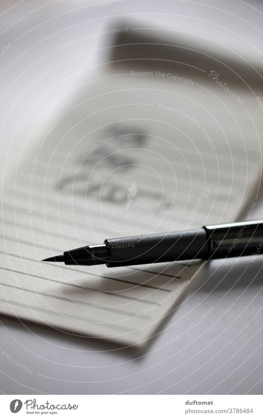 Black pen lies on lined piece of paper Piece of paper memo Paper Write Stationery Pen Interior shot Education Workplace School Office Office work