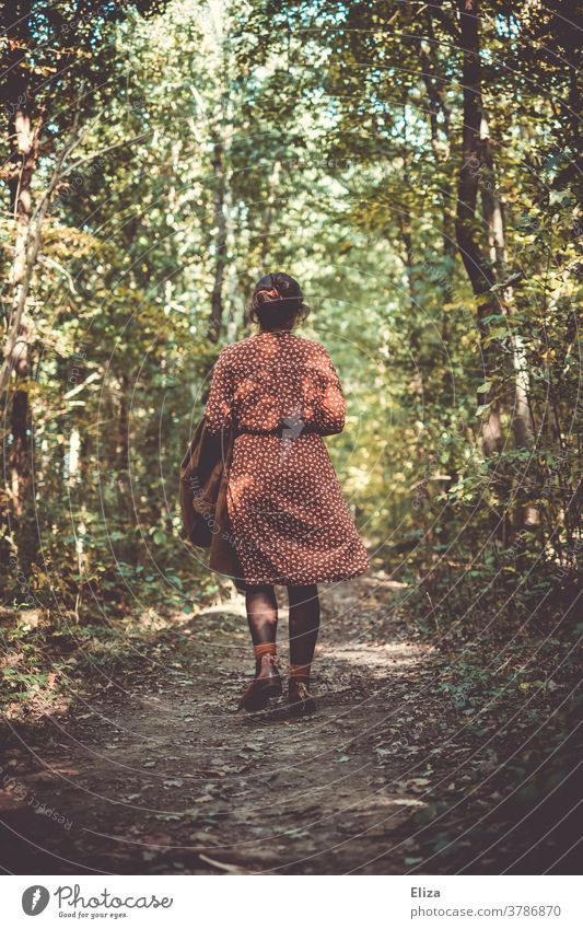 Woman in a red and white patterned dress walks in the forest in autumn. Forest To go for a walk Going Rear view Dress Forest walk Nature by oneself off