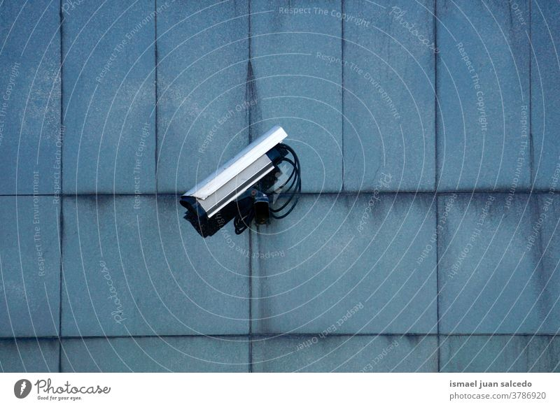 security camera on the building facade video camera wall background street surveillance equipment safety protection technology system control guard watching