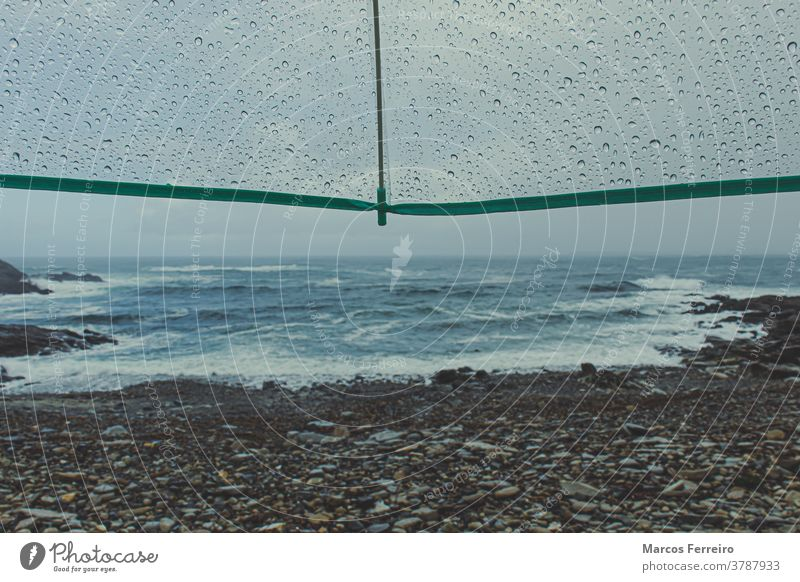 view of the coast with umbrella with raindrops water drop scene nobody alone shore dramatic protection waves coastline natural thunderstorm weather rainy autumn