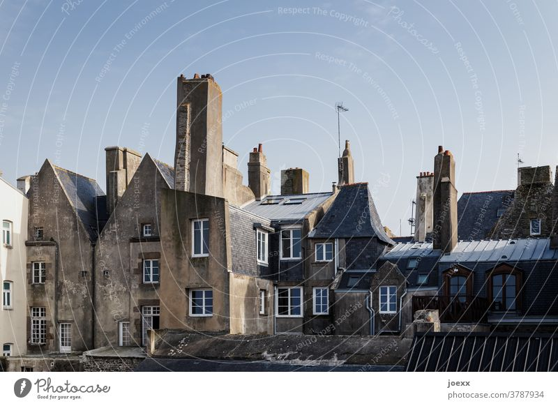 Facades of historic houses with chimneys in an old town Wall (barrier) Window Fireplaces Roof Sky Blue Village Old town Saint Malo France Brittany