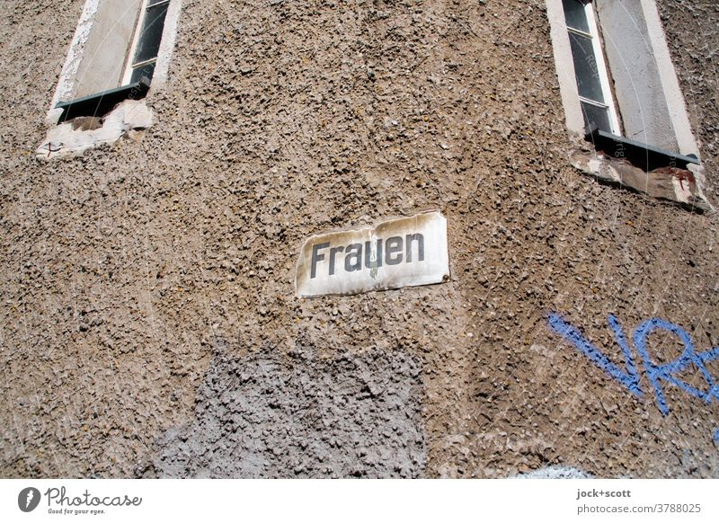 just women, a sign and two windows Facade Signs and labeling street sign Word GDR Wall (building) Window Ravages of time Weathered Typography Retro Past Plaster