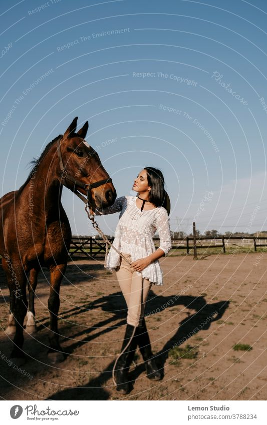 Latin woman touching a brown horse's head latina caressing free air field grass green sky blue trees vertical patagonia spring riding day animal horizontal