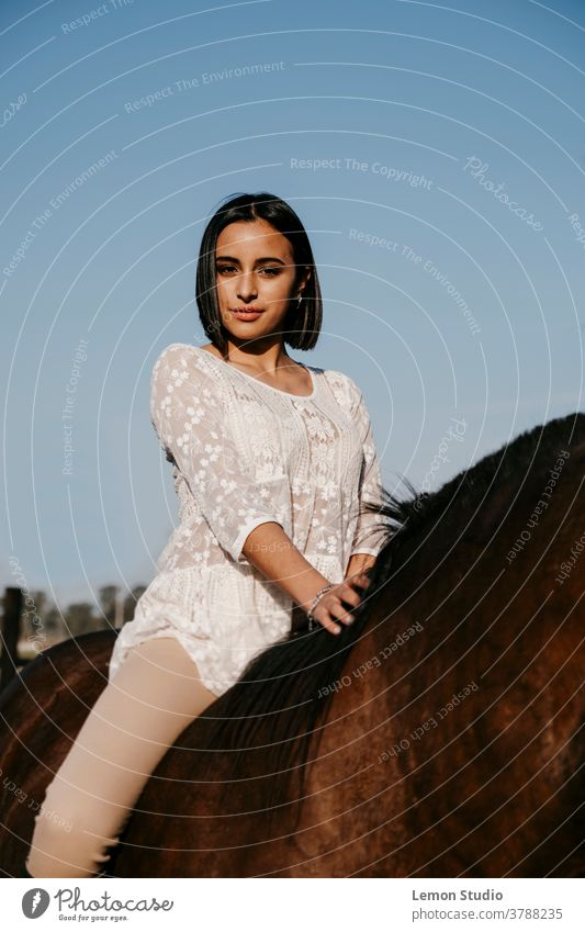 Latin American woman on a brown horse in front of the camera portrait Woman Free air Field Sky Blue Vertical Patagonia Spring Ride Day Animal white shirt