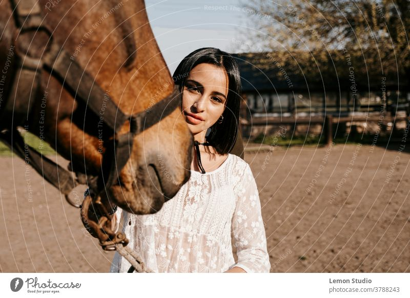 Close-up portrait of a Latina woman touching a horse animal brown team smile active lady rider equestrian elegance suit race background view luxury shirt nature