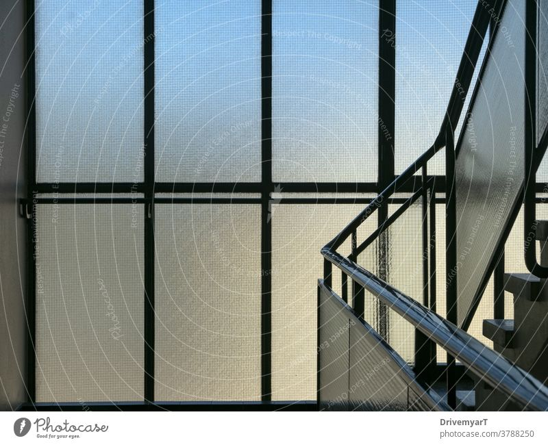 Window panes in building staircase with blue and yellow light coming through windows stairs stairway corridor hall interior background railing handrail modern