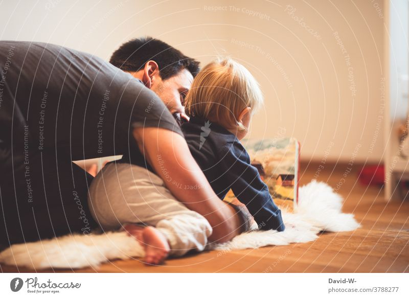 Father and son reading a book together Child Book look at Reading at the same time in common Love proximity Joy Infancy Together
