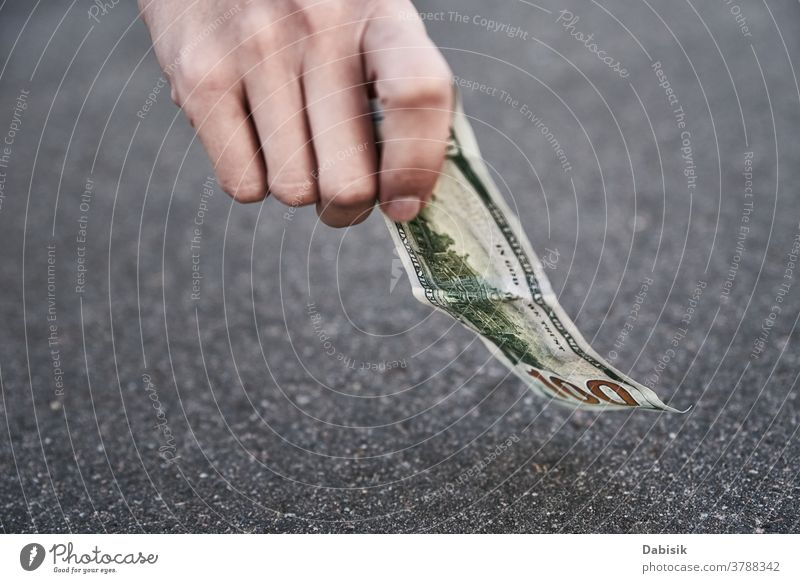 Hand pick one hundred dollar banknote from ground. Found money concept lost find street outdoor sidewalk person drop road cash bill woman currency hand luck