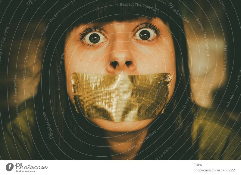 A woman whose mouth is taped shut, looks into the camera with her eyes wide open. Woman Fear Prohibition to speak Adhesive tape To be silent