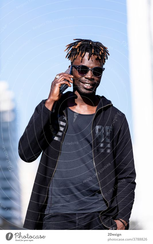 Black smiling man with sunglasses using mobile phone outdoors african black people male adult guy lifestyle happy photogenic 1 young technology casual attire