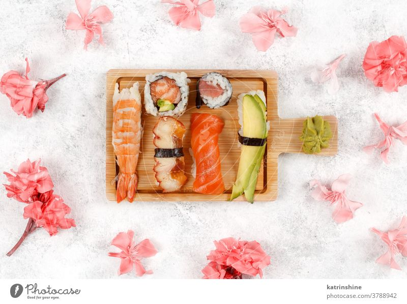 Sushi Set nigiri and sushi rolls on awooden board ready to eat eating Sashimi flowers pastel Rolls Maki sushi bar dinning Seafood plate top view Asian Prawn