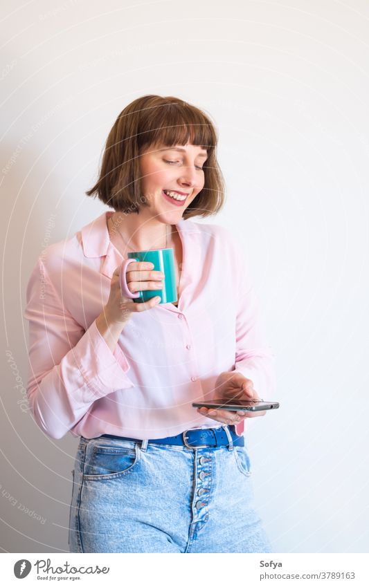 Woman drinking coffee and using smartphone woman device social media texting mobile phone smiling cup pink modern young positive optimist excited communication