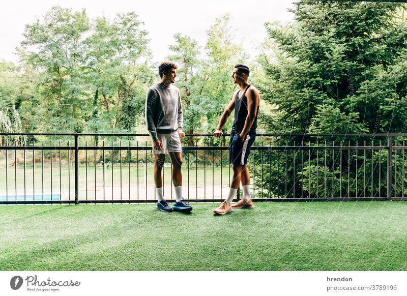two men dressed in sportswear talk after training at the gym people exercising two people young adult healthy lifestyle talking athlete health club males