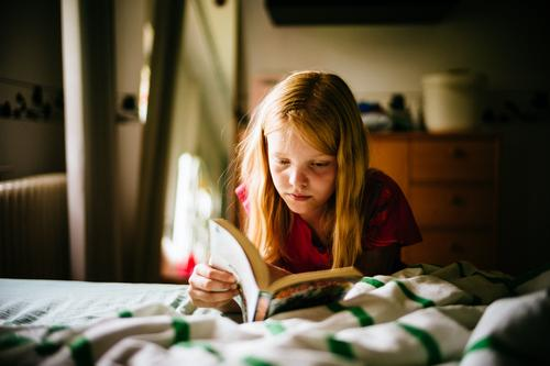 Child reads comics Infancy Reading Reading a book Comic portrait Book Colour photo Education Girl Interior shot Concentrate Human being Study Know Literature