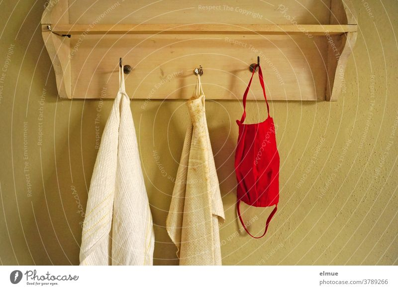 A red nose-mouth mask hangs next to two old, dirty towels on one of the three hooks of a wooden wardrobe Nose and face mask Mouth protection mask Mask Towel