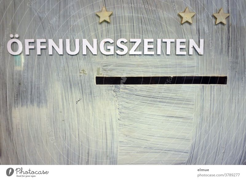 "The white lettering ""ÖFFNUNGSZEITEN"" and three golden stars are left - otherwise the white paint prevents the view through the glass pane opening hours Stars"