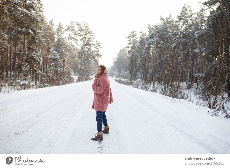 Young pretty stylish woman having fun in the winter snowy forest in motion. girl model happiness smile portrait adult attractive background beautiful beauty