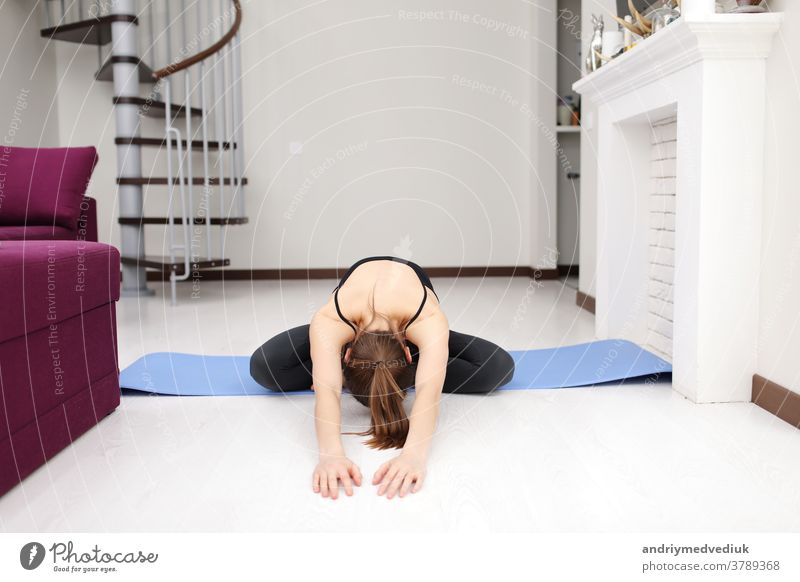 Does yoga exercises on mat on the floor. Young woman with slim body shape in sportswear have fitness day indoors at home. young girl stretch modern occupation
