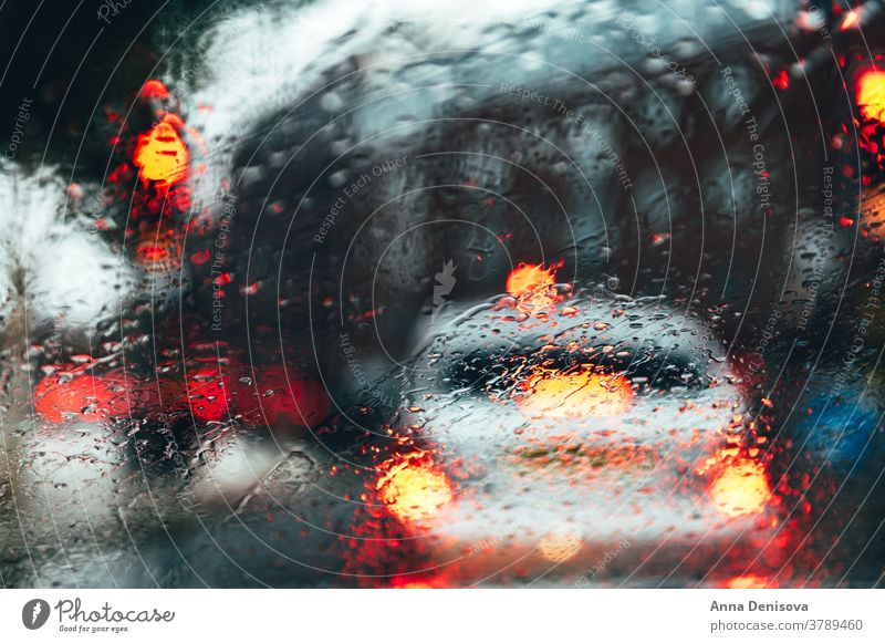 Blurred city street during dark rainy day blur blurry bokeh blurred background urban scene car motion abstract road downtown traffic light outdoor cityscape