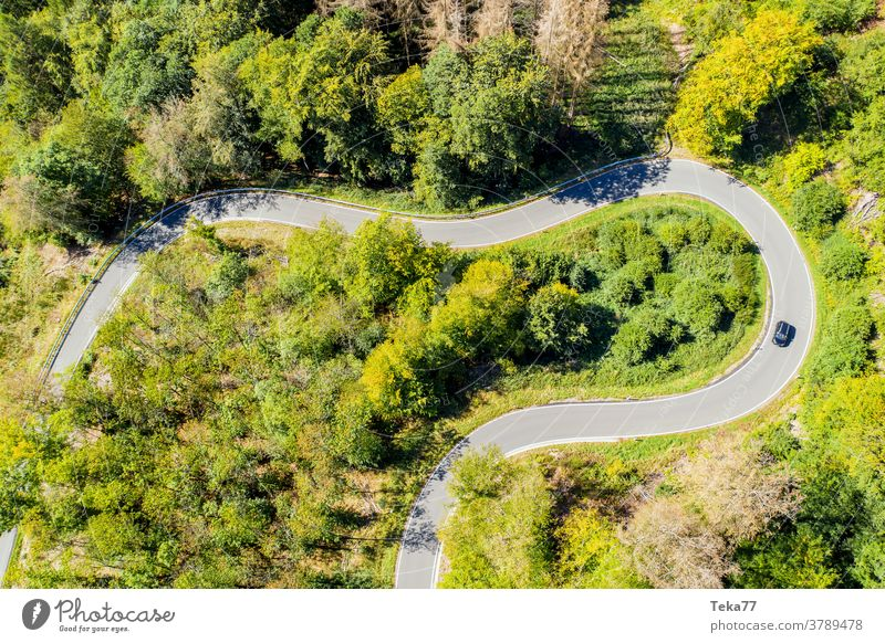 a car on a curvy forest road from above car from above forest from above street from above concrete summer countryside transportation sun shadow