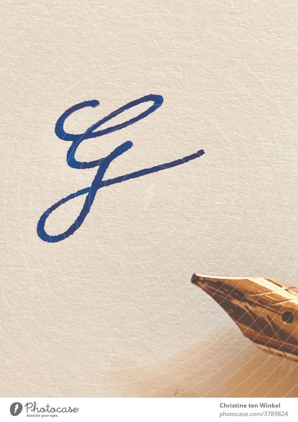 the squiggly letter G on light structured paper, written with blue ink. On the right edge of the picture you can see the golden tip of the fountain pen