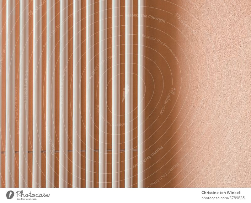 Vertical tubes of a radiator on a light apricot coloured wall with light and shadow Heater Pipe Wall (building) Shadow Shadow play apricot-coloured White