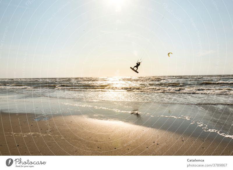 Kiter on the beach rises from the water into the air Beach Blue Sand Sandy beach Kitesurfing vacation Sports Ocean Horizon Sky North Sea Waves Surf coast Sun