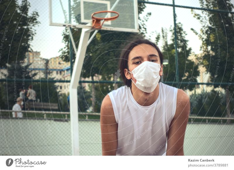 Teenager wearing a protective mask resting in front of basketball hoop young male man sport outdoor net tired masked handsome Authentic Basketball player