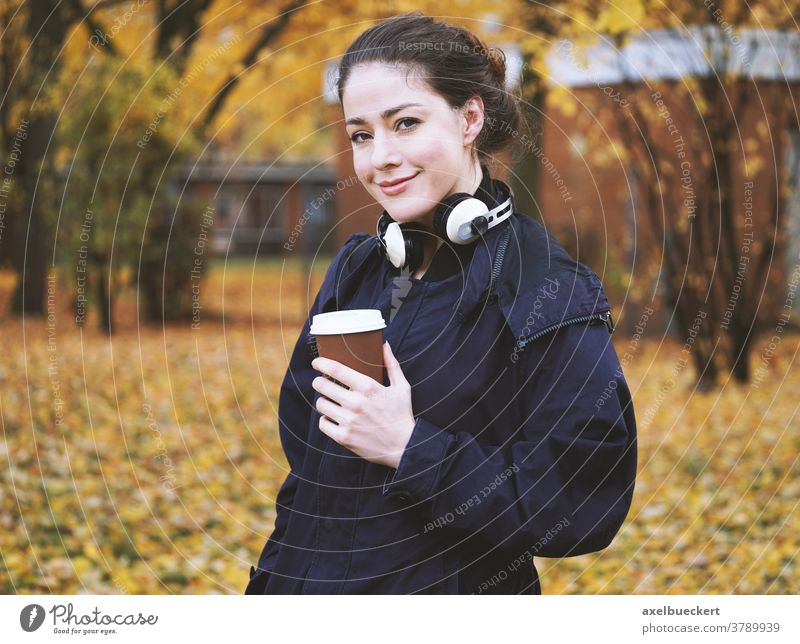 young woman with coffee to go cup and headphones in autumn candid outdoor outside real people fall hot drink cold weather street walk park disposable holding