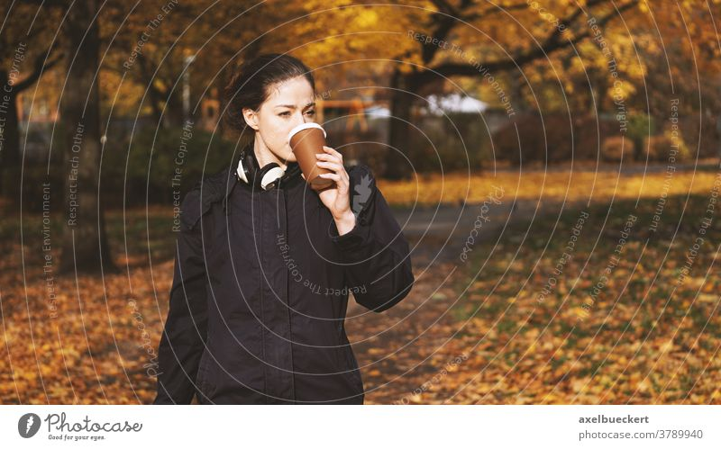 young woman drinking coffee to go while on the move take out lifestyle people outdoor candid real people autumn fall hot beverage disposable cup walking park