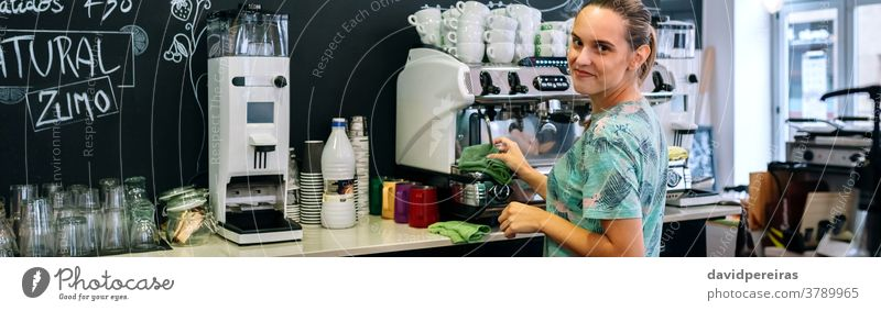 Smiling waitress cleaning coffee maker coffee machine coffee shop looking camera smiling banner header web panorama panoramic dishcloth restaurant cafeteria