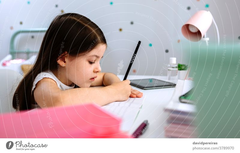 Girl doing homework sitting at a desk girl writing homeschooling school at home quiet wrong pencil posture closeup bedroom covid-19 online child beautiful cute