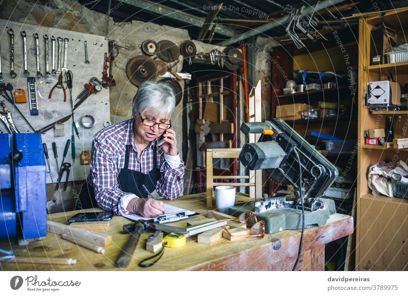 Female carpenter in her workshop carpentry woman senior talking mobile cell phone custom made business mature writing wood people old caucasian artisan aged