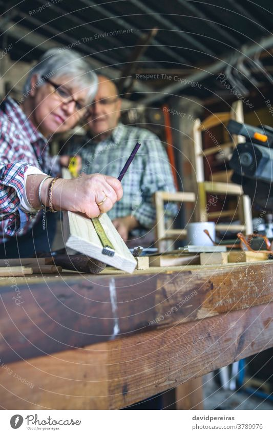 Senior couple in a carpentry senior woman measuring metre mark plank wooden batten workshop together collaborate working helping hobby carpenter occupation