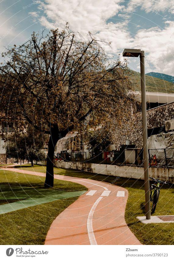 Radweg durch eine Grünanlage am Gardasee gardasee vacation radweg grünanlage garten park fahrrad natur bäume Berge sommer sonne laterne urban straße verkehr