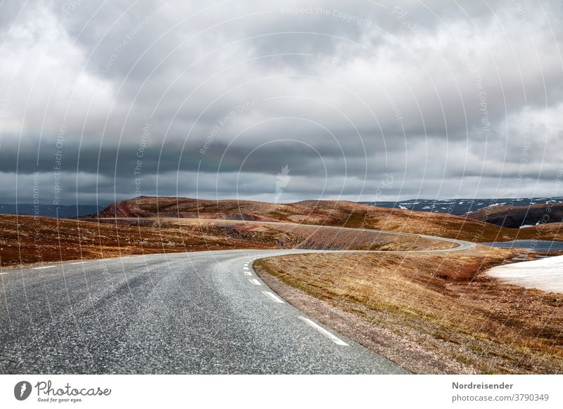 Lonely country road over the mountains of Varanger in Norway Street Loneliness mysticism Curve Transport fjell High mountain region Asphalt Grass treeless