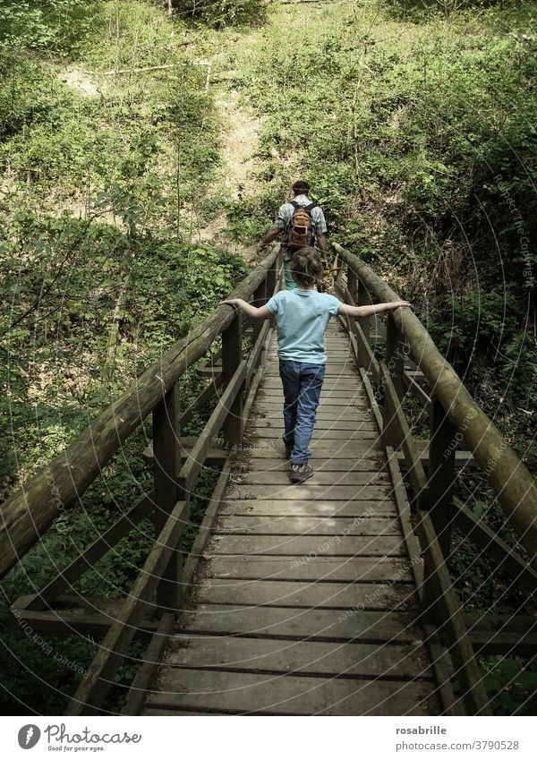 spaces   child walks behind father over a wooden bridge Wooden bridge Child Father Bridge ensue Trust To hold on Going Hiking stroll togetherness