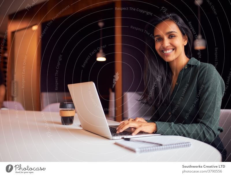 Portrait Of Businesswoman Sitting At Meeting Table Working On Laptop In Modern Open Plan Office business businesswomen meeting office sitting boardroom table